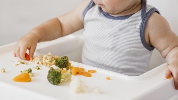 Bé ăn dặm tại bàn ăn với súp lơ và cà rốt