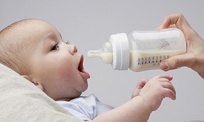 Mẹ đưa núm vú bình sữa vào miệng bé khi thấy bé mở miệng to nhé!