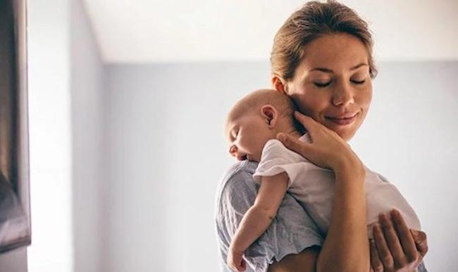 Mẹ đặt bé trên vai và vỗ nhẹ nhàng để đẩy không khí thừa trong bụng bé ra ngoài.