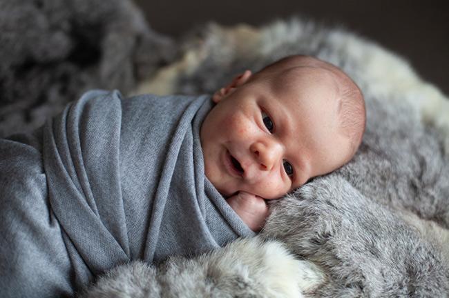 Sau khi bé tắm xong, mẹ quấn khăn để ủ ấm cho bé.
